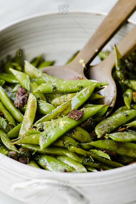 Close-up of fried pea pods with wooden spoons in container
