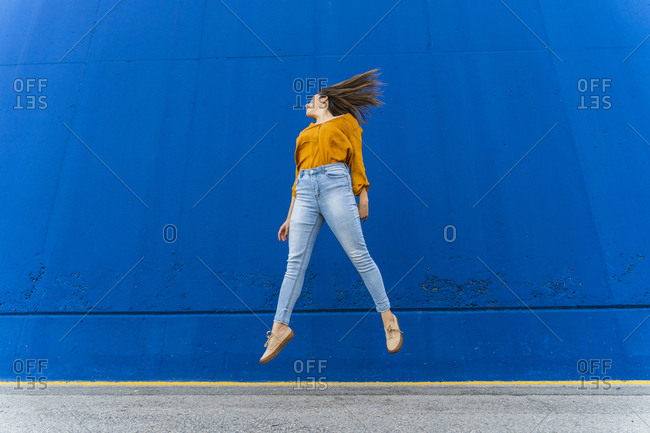 Young woman jumping in front of a blue wall