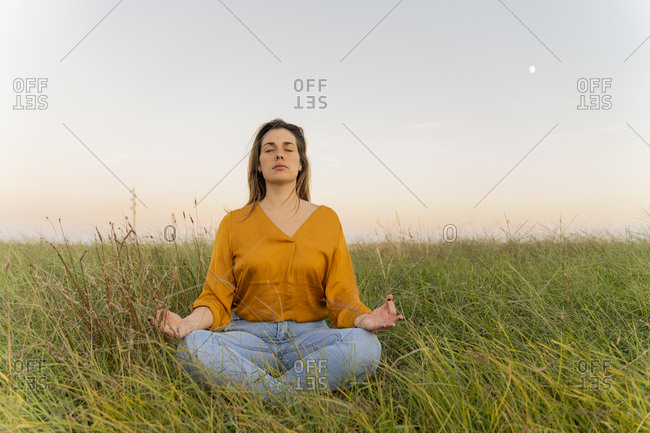 Young woman sitting on a meadow and meditating in the evening
