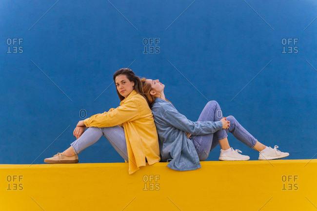 Young beautiful carefree women sitting on an orange wall