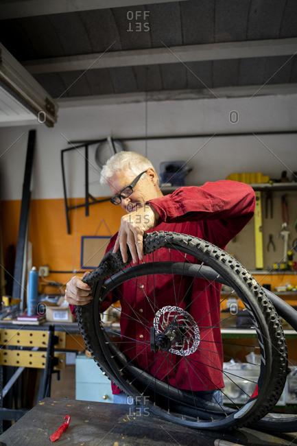 Senior man repairing bicycle tire in garage