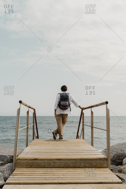 Rear view of traveler standing on wooden boardwalk