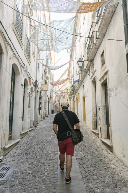 Tourist walking in an alley in the old town of Coimbra- Portugal