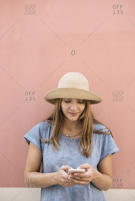 Woman standing at a pink wall using smartphone