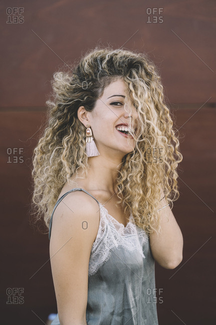 Portrait of laughing young woman with dyed blond ringlets