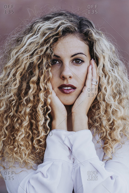 Portrait of young woman with dyed blond ringlets