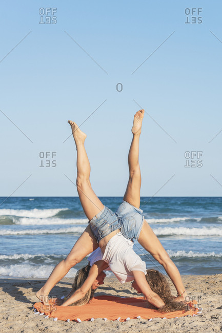 Two women practicing Acro Yoga on the beach- downward facing dog position