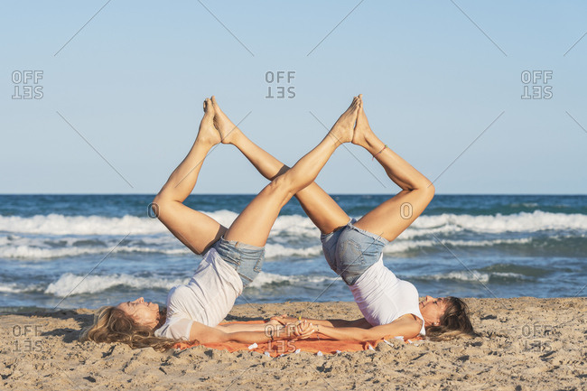 Two women practicing Acro Yoga on the beach