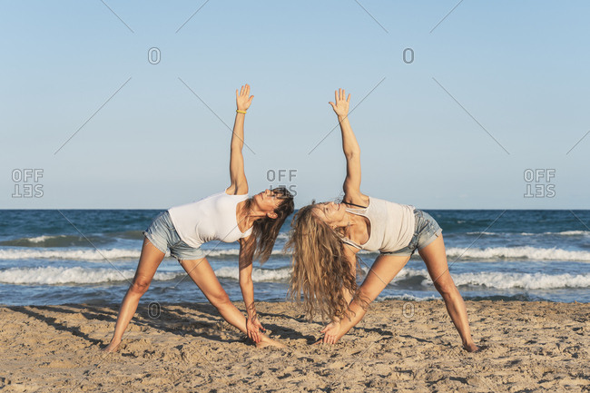 Two women practicing Acro Yoga on the beach- triangle pose