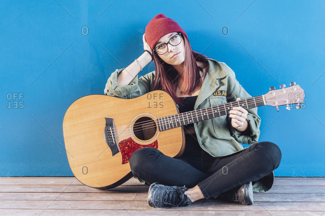 Teenage girl with guitar sitting on wooden floor