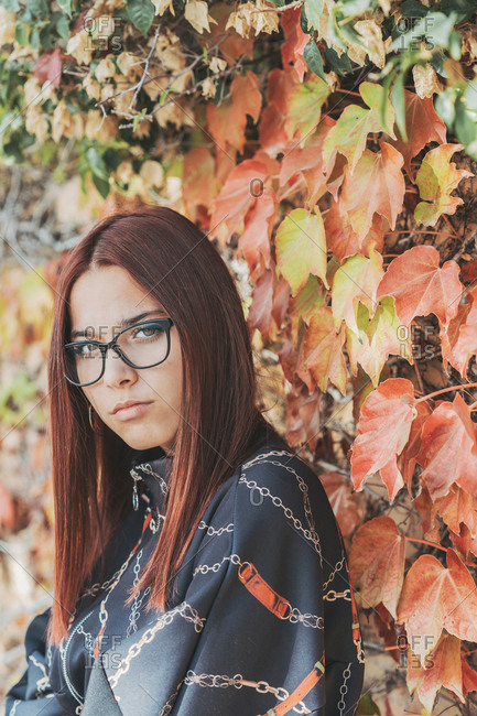 Portrait of teenage girl with dyed red hair in front of greening in autumn