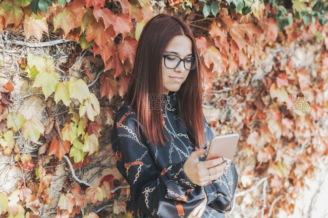 Portrait of teenage girl with dyed red hair checking smartphone in autumn
