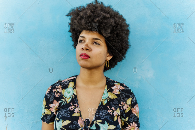 Portrait of Afro-American woman looking sideways- blue wall in the background