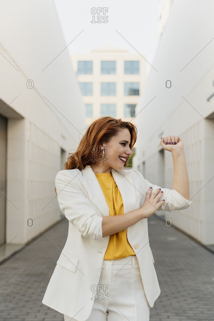 Energetic businesswoman in white pant suit- flexing her muscles