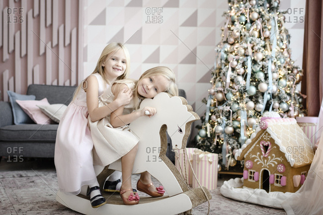 Portrait of happy two little girls together on a rocking horse at Christmas time