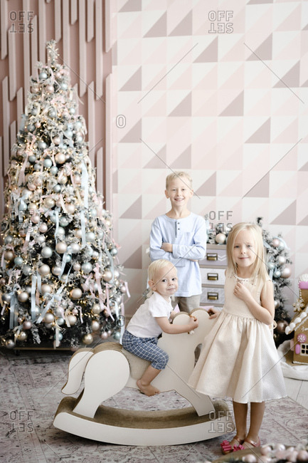 Group picture of three children in front of Christmas tree