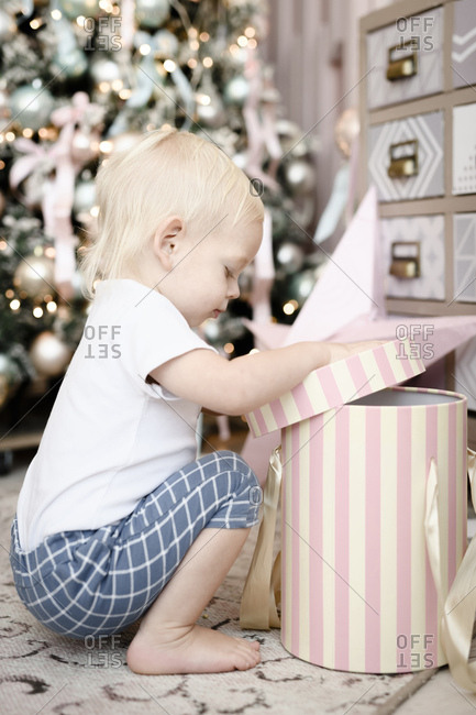 Toddler opening gift box in front of Christmas tree