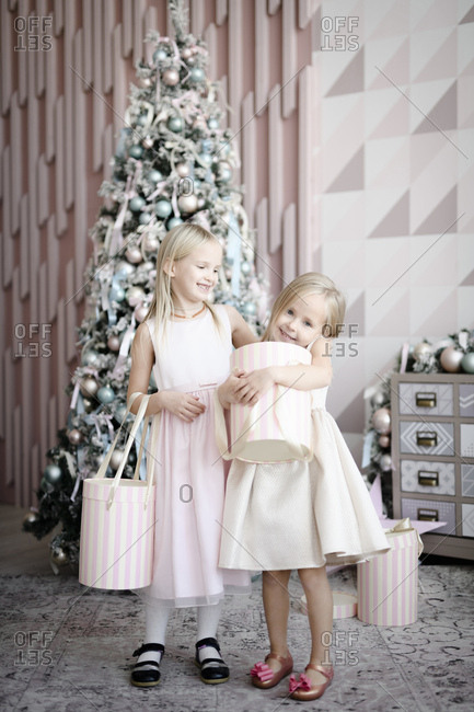 Portrait of two happy little girls standing in front of lighted Christmas tree with gift boxes