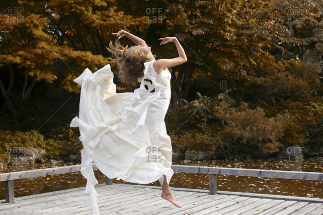 Ballerina wearing white dress and jumping on wooden jetty