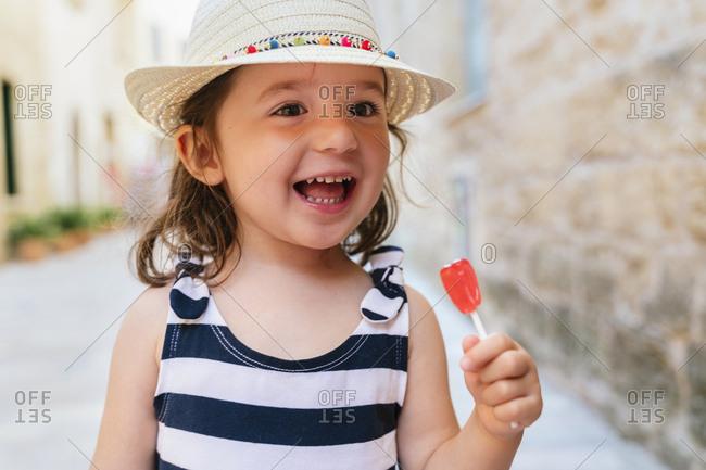 Portrait of happy little girl with red lollipop in summer