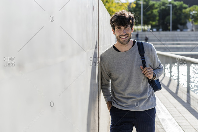 Portrait of smiling man with backpack having a break in the city