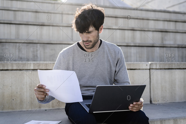 Man sitting on outdoor stairs using laptop and reviewing paper