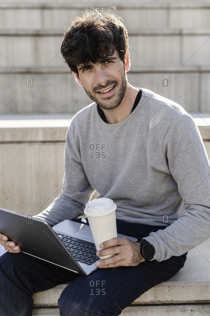 Man sitting on outdoor stairs with takeaway coffee and laptop