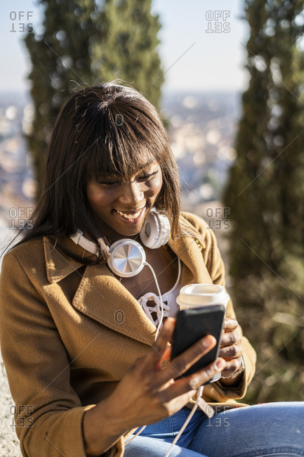 Smiling female tourist looking at her smartphone outdoors