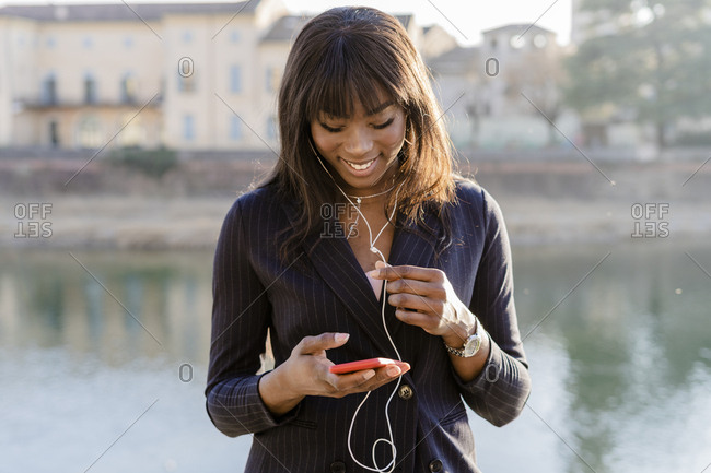 Smiling businesswoman using her smartphone outdoors