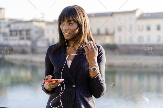 Businesswoman using her smartphone outdoors