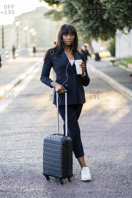Portrait of a businesswoman with suitcase and coffee to go outdoors