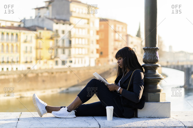 Businesswoman sitting outdoors using a digital tablet
