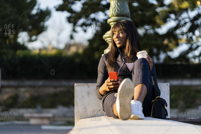 Smiling businesswoman sitting outdoors using her smartphone