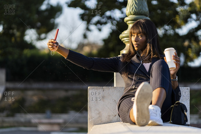 Smiling businesswoman sitting outdoors making a selfie