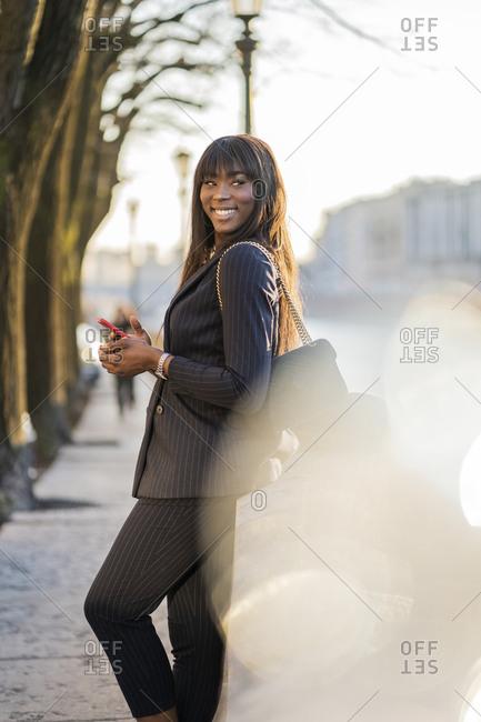 Smiling businesswoman standing at rivershore