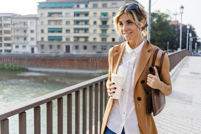 Smiling woman with earphones and coffee to go walking through city