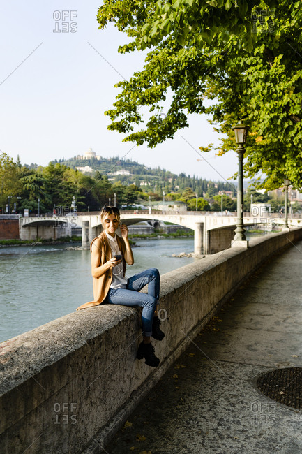 Woman with earphones sitting at riverside using smartphone