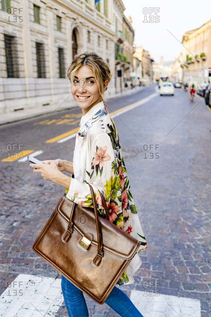 Smiling woman with smartphone walking through the city