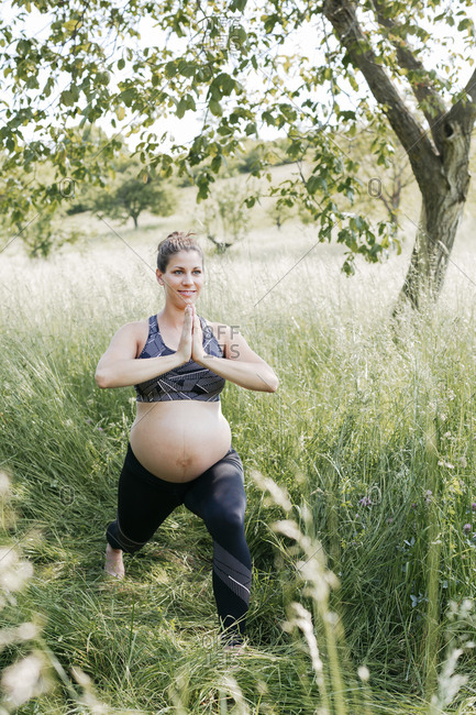 Young pregnant woman doing yoga exercises in nature on a green meadow