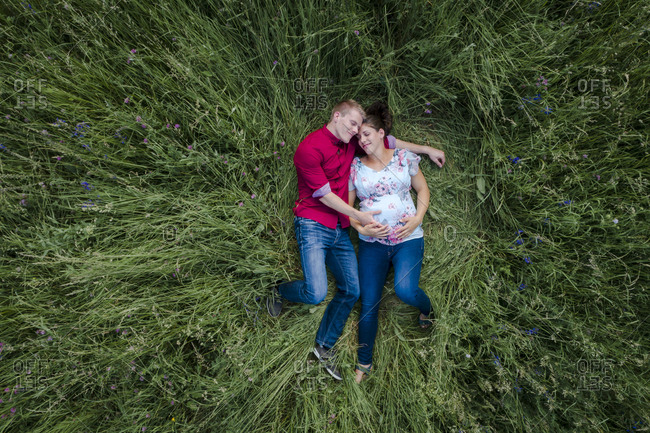 Pregnant woman and man holding baby belly- lying on meadow