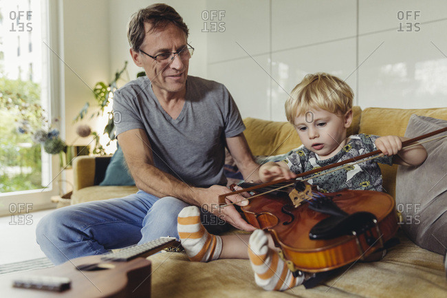 Portrait of toddler testing violin while his father watching