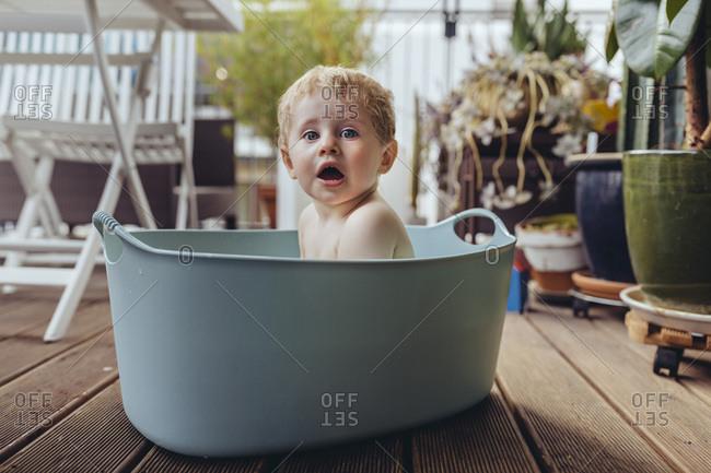 Baby boy sitting in baby bath on the balcony