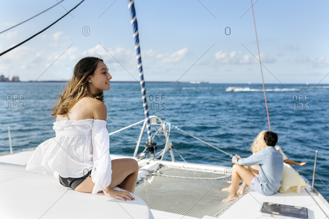 Three young friends enjoying a summer day on a sailboat