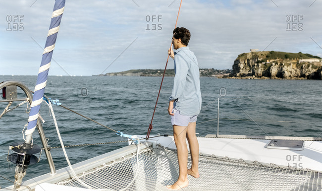 Young man standing on a sailboat