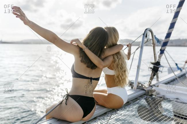 Two beautiful women enjoying a summer day on a sailboat