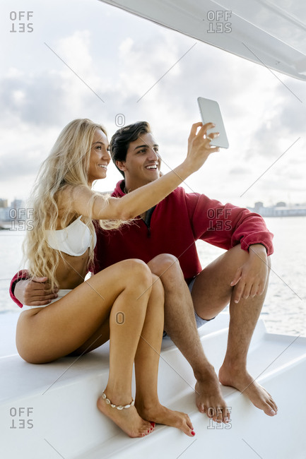 Young couple enjoying a summer day on a sailboat