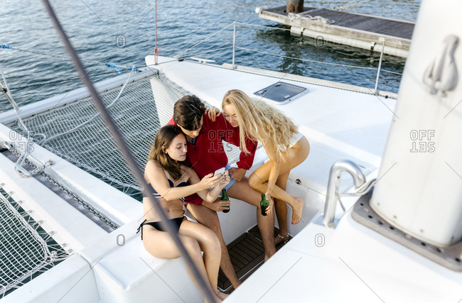 Three young friends enjoying a summer day on a sailboat- taking a selfie