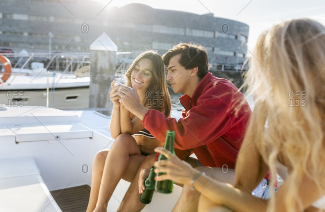 Three young friends enjoying a summer day on a sailboat and using smartphone