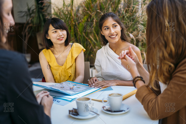 Female multicultural students meeting in a cafe organizing their class schedule
