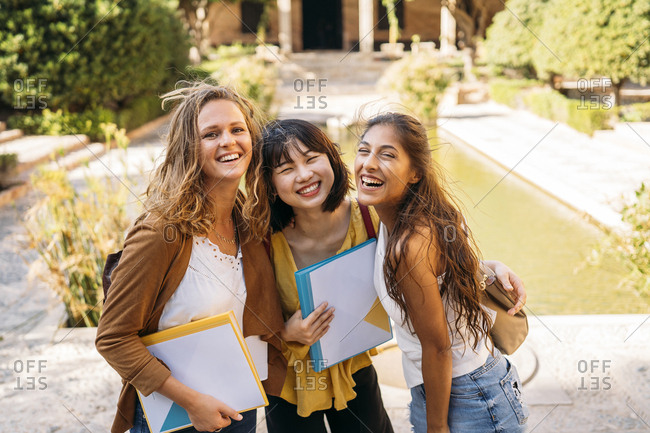 Portrait of three happy female friends visiting a formal garden